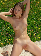 Nastya exposes her youthful beauty in a field covered with flowers